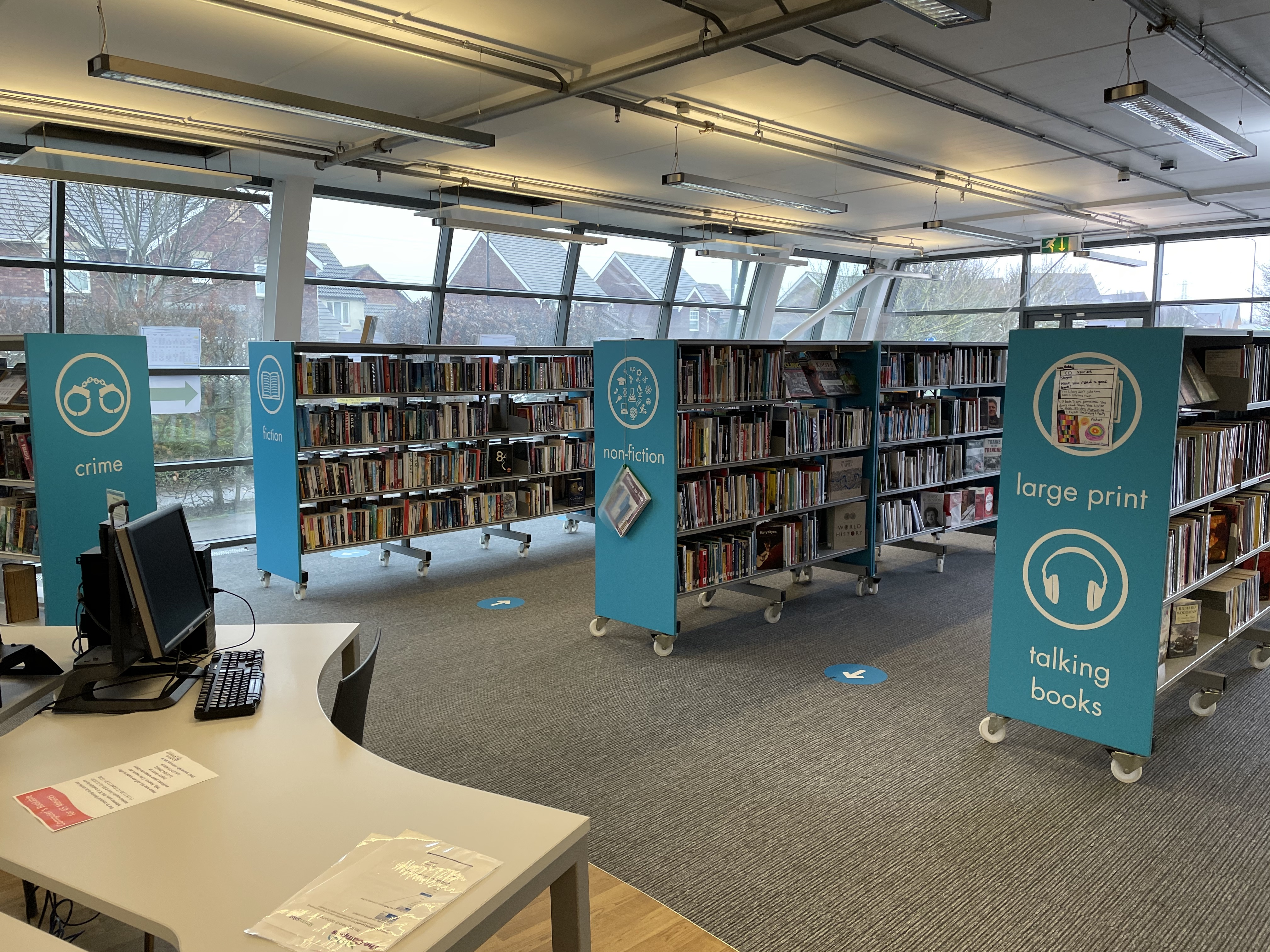 An interior image of the Campus library, with bright blue shelves and books and grey carpet