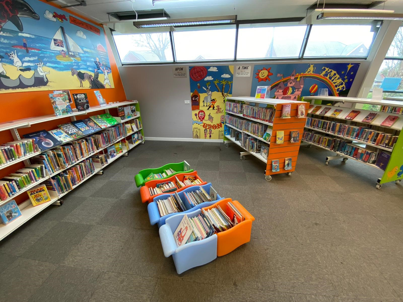 A side view of the children's area at a library, with orange and green shelves and book bins
