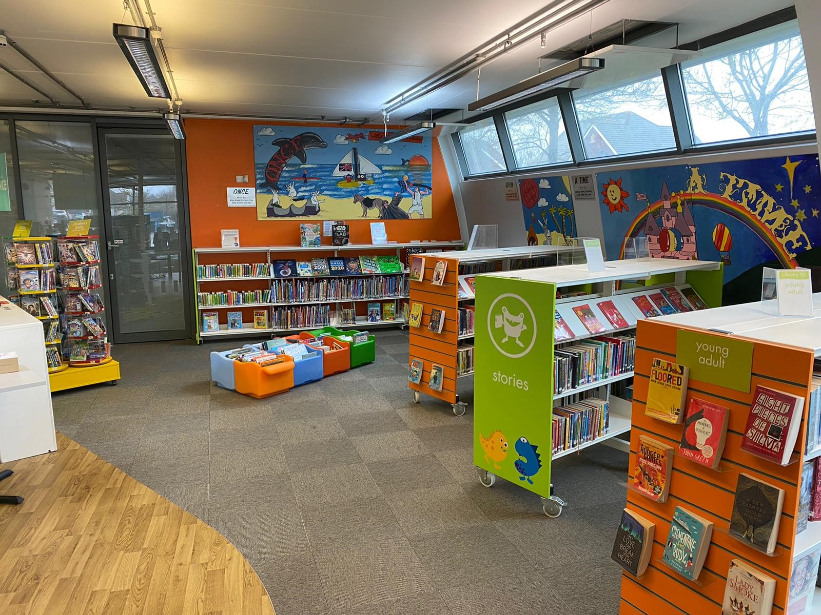 An interior of a children's area at a library, with colourful paintings on the walls and books on the shelves